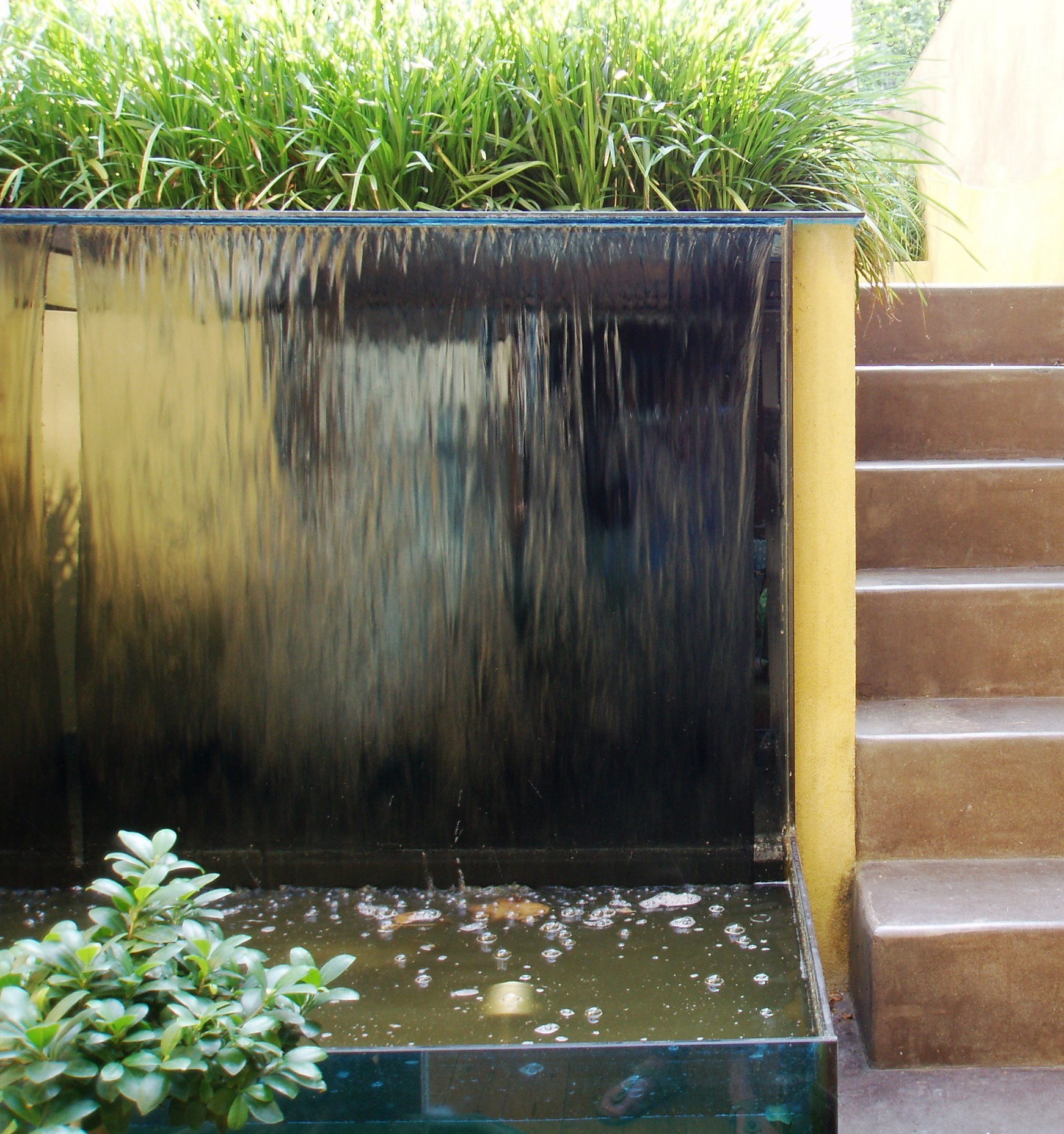 Garden with glass water wall and polished concrete steps for Wall water fountain